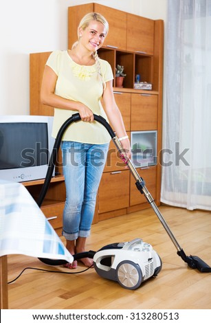 happy woman using vacuum cleaner during regular clean-up - stock photo