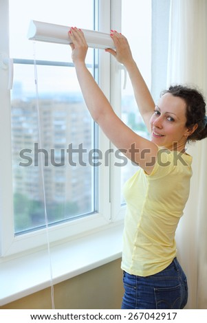 Happy woman wants to hang blinds on the window - stock photo