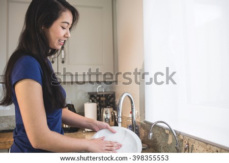 Happy woman washing up in the kitchen at home - stock photo