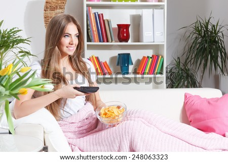 Happy woman watching TV with snacks - stock photo