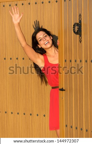 Happy woman waving and opening country house door to welcome guests visitors. Charming caucasian brunette girl good bye standing in home entrance. - stock photo