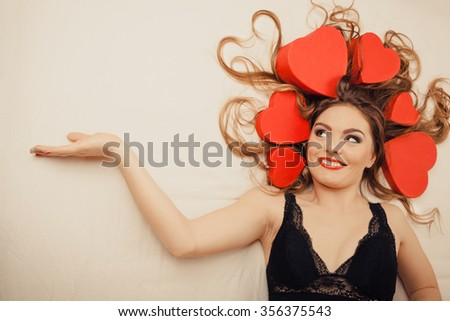Happy woman wearing lingerie in bed at home showing empty blank copyspace. Attractive seductive young girl with heart shape boxes around head. Female underwear fashion. Valentines day love. - stock photo