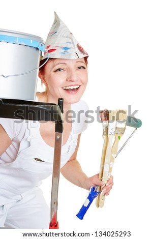 Happy woman while painting with brushes and a ladder - stock photo