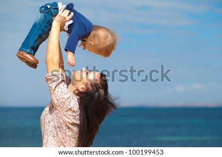 Happy woman with a child resting on the nature on the sea beach - stock photo