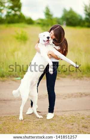 Happy woman with a dog having fun outdoors outside the city - stock photo