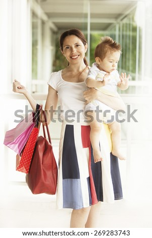 Happy woman with baby and shopping bags - stock photo
