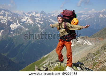 Happy woman with backpack standing on a mountain jad - stock photo