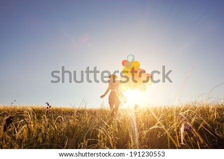 Happy woman with balloons running on the green field at sunset. - stock photo