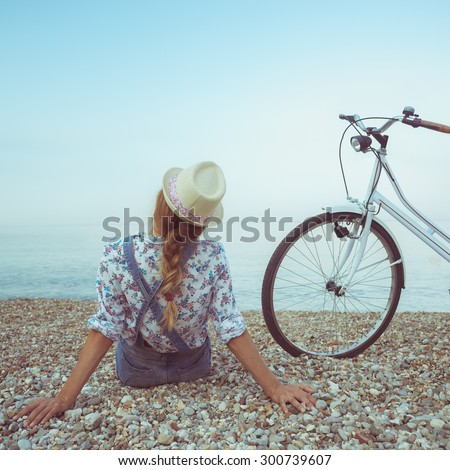 Happy woman with bicycle on the beach - view from the back - stock photo