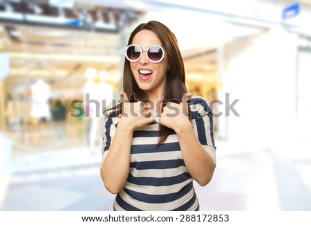 Happy woman with both thumbs up. She is wearing white sunglasses. Over shopping center background - stock photo