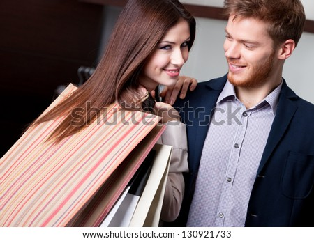 Happy woman with boyfriend after shopping smiles - stock photo