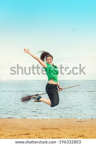 Happy woman with broom jumping on the beach - stock photo