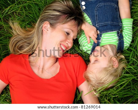 Happy woman with child on the green grass - stock photo