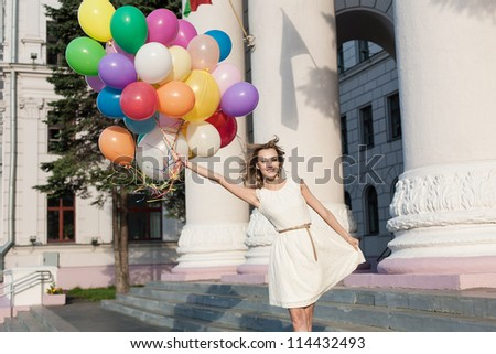Happy woman with colorful latex balloons keeping her dress, urban scene, outdoors - stock photo