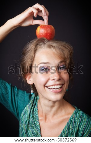 Happy woman with healthy teeth and apple on head - stock photo