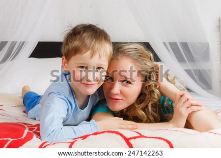 Happy woman with her child laying on belly on bed - stock photo