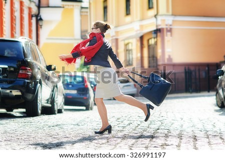 happy woman with hurry a bag crosses the street. - stock photo