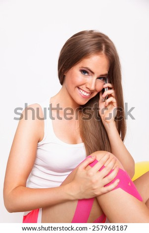 Happy woman with injured leg on the phone - stock photo