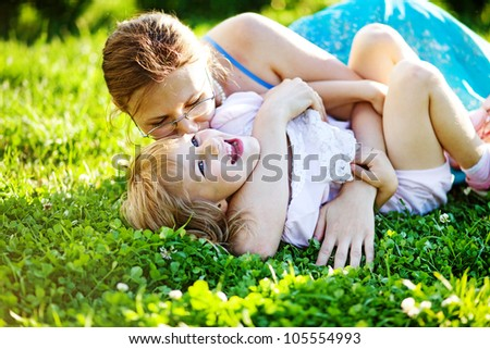 Happy woman with kid outdoors - stock photo