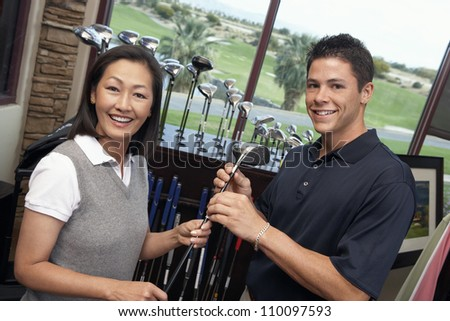 Happy woman with man selecting golf club in store - stock photo