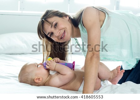 Happy woman with playful son on bed at home - stock photo