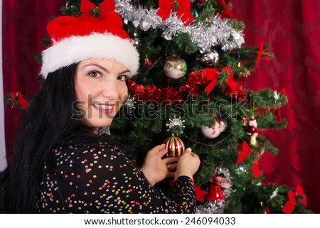 Happy woman with santa hat decorates Christmas tree - stock photo
