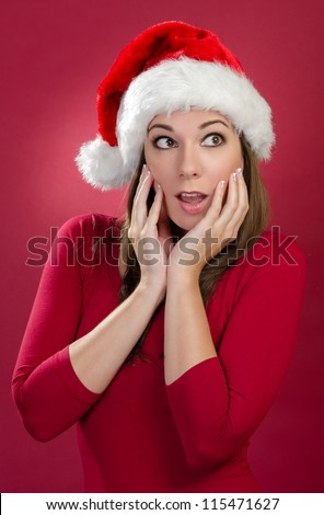 Happy woman with Santa Hat on a red background - stock photo