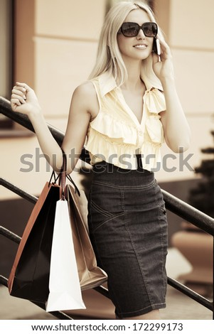 Happy woman with shopping bags calling on the cell phone - stock photo