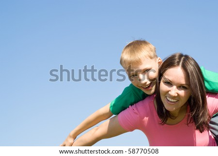 happy woman  with  son on a background of sky - stock photo