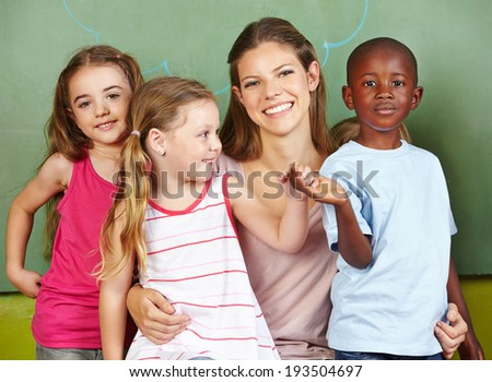 Happy woman with three different children in a kindergarten - stock photo