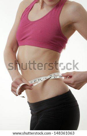 happy woman with thumbs up in a sports bra looking happy - stock photo