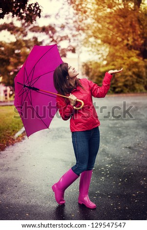Happy woman with umbrella checking for rain in a park - stock photo