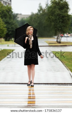 Happy woman with umbrella walking on the rainy city street - stock photo