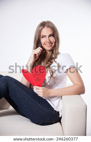 Happy woman writing a love card - stock photo