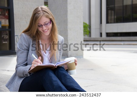 Happy woman writing in her journal - stock photo