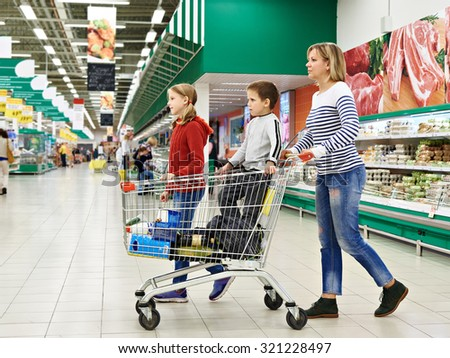 Happy women and children with cart shopping in supermarket - stock photo