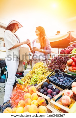 Happy women choosing a fruit outdoors in the bio market. Lens flare and Shallow Doff - stock photo