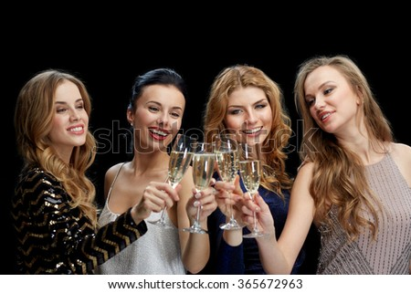 happy women clinking champagne glasses over black - stock photo