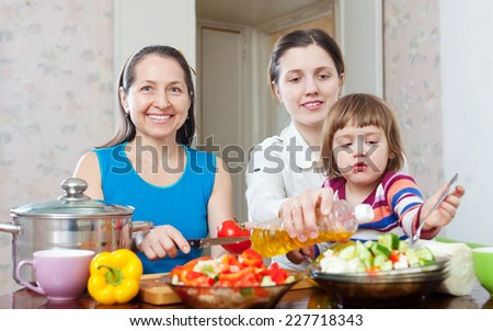 Happy women cook vegetables, while baby eats salad  in the kitchen - stock photo