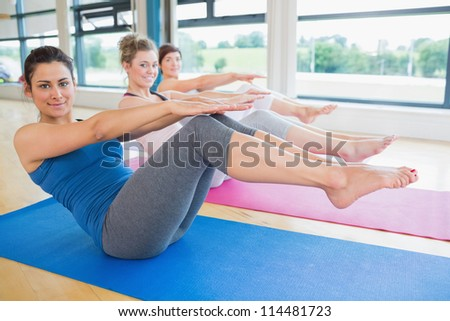 Happy women doing boat pose in yoga class in fitness studio - stock photo