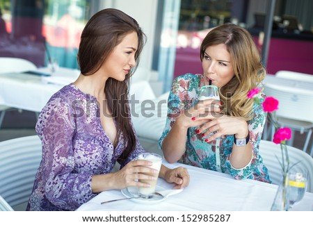 Happy women drinking coffee and talking - stock photo
