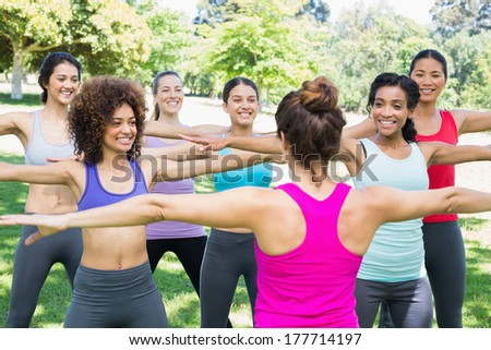 Happy women exercising with female instructor at park - stock photo