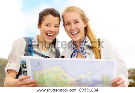 Happy women hold map and laugh. fun outdoor adventure lifestyle concept. - stock photo