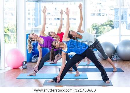Happy women in fitness studio doing side stretch on exercise mat - stock photo