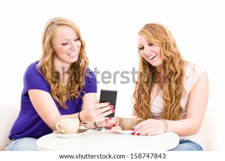 happy women looking at a smartphone sitting at a coffee table on white background - stock photo