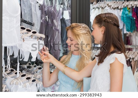 Happy women looking at underwear in shopping mall - stock photo