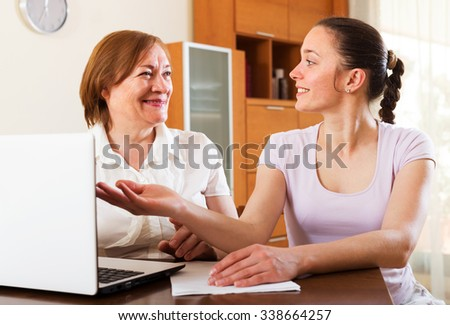 Happy women looking financial documents in laptop at table in home or office interior - stock photo