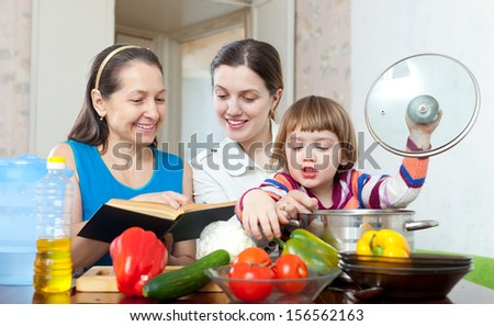 Happy women of three generations cook vegetables in the kitchen at home - stock photo