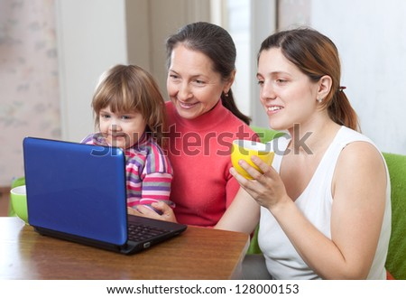 Happy women  of three generations using laptop on sofa  in home - stock photo