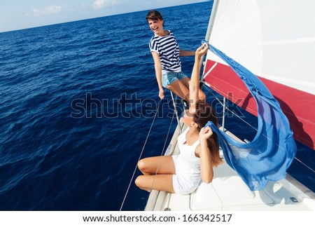 Happy women on the bow of a Sailboat.Copy space - stock photo